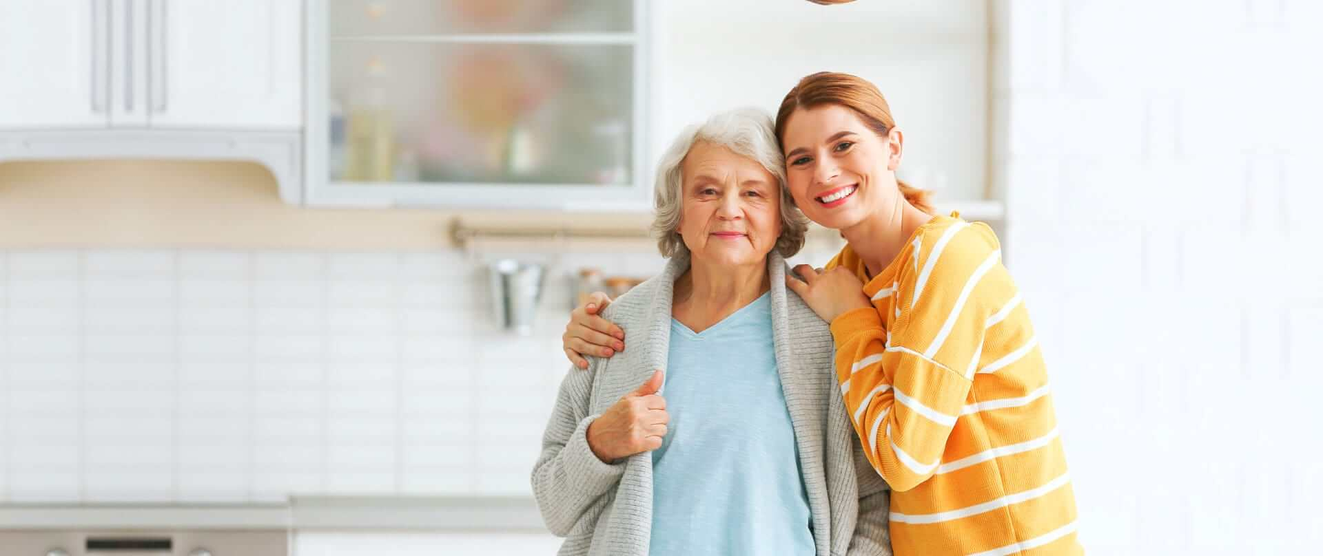 portrait of caregiver and senior woman at the kitchen