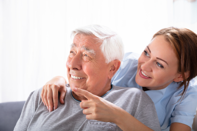 caregiver and the elder man looking at something