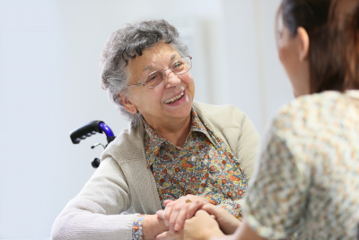 caregiver helping the elder lady on the wheelchair