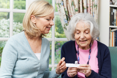 caregiver helping the elderly woman on her medication